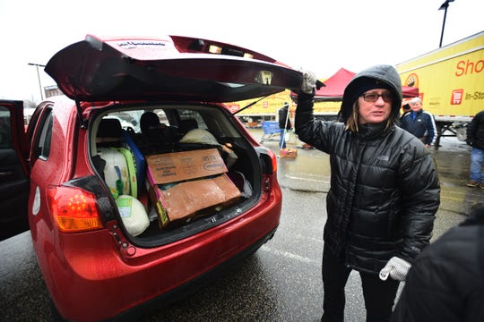 Employees of Inserra ShopRite supermarkets including Vera Kovalski, helps to load boxes of turkeys into a car as they are giving away 8,500 turkeys to needy families, at the parking lot in Lodi on 12/17/19.