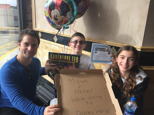 Thomas Head, founder and chief executive officer of Childhood Cancer Society, surprises cancer survivor Mason Sneed and his sister, Hazel, with a trip to Walt Disney World at a Wayne pizzeria.