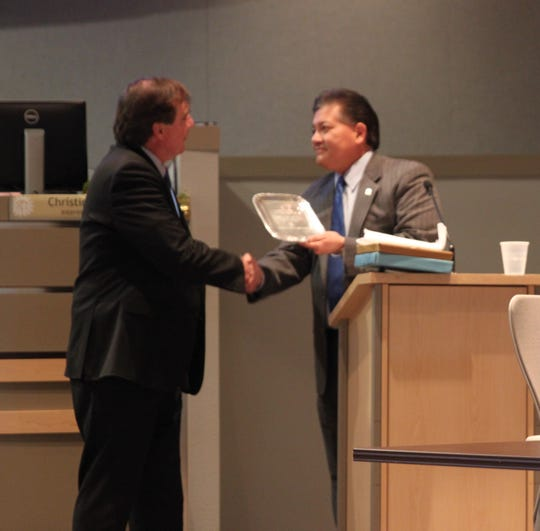 City Councilor Greg Smith, left, receives a thanks and an engraved plate from Mayor Ken Miyagishima on Smith's last day as a city councilor on Dec. 16, 2019.