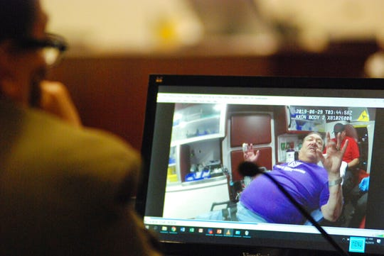 In this photo taken Monday, Dec. 16, 2019, New Mexico state Sen. Richard Martinez, left, and on screen, watches a prior police body-camera video of himself during his trial on drunken driving charges at a state court in Santa Fe, N.M. Martinez has pleaded not guilty to charges of reckless driving and aggravated driving while intoxicated after a crash in June in which he rear ended a stopped car at a red light. Martinez's attorney says he apparently hit his head in the car wreck and was dazed as he struggled with sobriety tests.