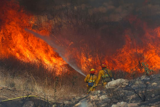 Firefighters battle the flames of the Hill Fire as it approaches homes in the foothills of Jurupa Valley, Calif., October 30, 2019. Fire and weather officials say the 2020 wildfire season may begin early due to a lack of rain in January and February.