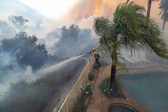 A firefighter works to keep flames at away from a house that was being threatened by the Tenaja fire in the Murrieta foothills on Single Oak Way, September 5, 2019.