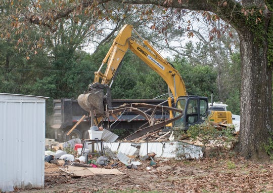 A demolition crew knocks down structures at Flamingo Park as residents are being forced to vacate the property on 9 Mile Road in Pensacola on Monday, Dec. 16, 2019.