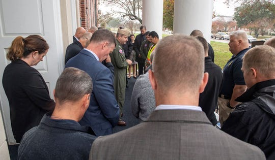 Base Commander Tim Kinsella (pictures center, in flight suit) holds a moment of silence on the steps of the classroom building where 11 people were gunned down in a shooting rampage Dec. 6. Three people died and 8 additional people were injured. The gunman also died. The FBI has turned the building back over to the Navy after announcing its search for physical evidence was complete.