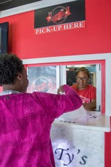 Aunt Doris Jones hands an order to a customer at Family Ty's restaurant on Nine Mile Road in Pensacola on Tuesday, Dec. 17, 2019.