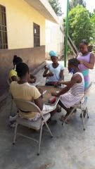 Girls in Source of Life Ministries play dominoes. In Haiti, every time you lose in dominoes you must place a clothes pin on your face, ears, arms or chest.