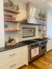 Small Christmas trees in burlap bags on the open shelving in the kitchen make the space feel warm and festive.