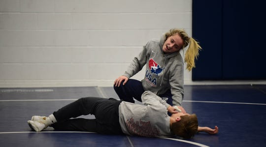 West York's Carly Gross laughs with a teammate while doing drills at practice. Gross is one of a handful of girls' wrestlers in the YAIAA.