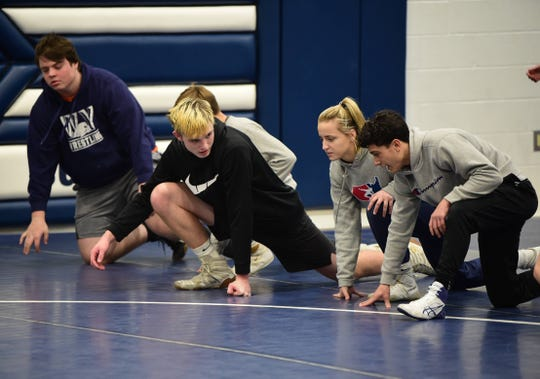Carly Gross talks with teammates Elijah Lawless (left) and Ivan Vega (right) at practice on Tuesday, Dec. 17. Gross was the first commit to Lock Haven's inaugural girls' wrestling recruiting class.