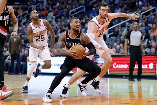 Portland Trail Blazers guard Damian Lillard drives past Phoenix Suns forward Frank Kaminsky (8) and forward Mikal Bridges (25) during the first half of an NBA basketball game, Monday, Dec. 16, 2019, in Phoenix.
