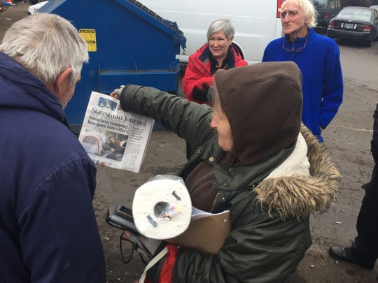 "Donna Smith, center, shows a copy of the Statesman Journal with herself on the front page. Anne Wilson, center back, was ""heartbroken"" by the sight of the homeless camp at The ARCHES Project in Salem, and decided to deliver supplies to Smith. Photographed Tuesday, Dec. 17, 2019."