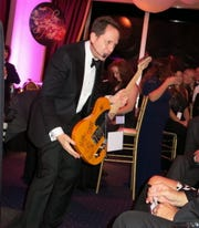 DAC Live Auction Auctioneer David Goodman, of Chicago, attempts to persuade a live auction bidder to go higher for yellow Squier Bullet electric guitar by Fender. It was signed by Rolling Stones.    High bid? $7,500.