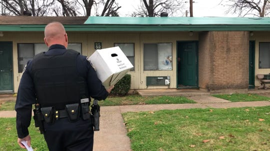 Bossier Sheriff's Sgt. Tony Broadway carries a Spirit of Christmas Food Drive box to a residence in Bossier City on Tuesday, Dec. 17, 2019.