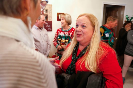 Nancy Johnson greets friends at the door during her annual holiday open house where she collects food donations for families in need.