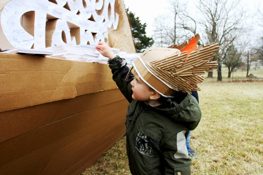Four-year-old Theo Pallardy places his handwritten regret onto a cardboard Viking ship in Rogersville Dec. 14, 2019.