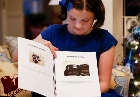 Sixth-grader Ellie Rowe, who has diabetes, shows a draft of her book that she originally wrote for a class project as a guide to managing the disease for kids. Rowe is now working with a publisher to bring the book to print.
