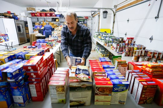 Jeff Tiefenbrunn sorts donated food items at a friend's holiday open house on Saturday, Dec. 14, 2019. Her friends, Nancy and Greg Johnson, collect the food items for families in need.