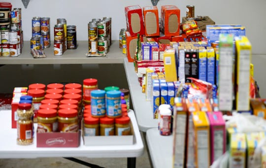 Donated food items sit on tables during an annual holiday open house put on by Nancy and Greg Johnson on Saturday, Dec. 14, 2019. The Johnsons collect the food items for families in need.