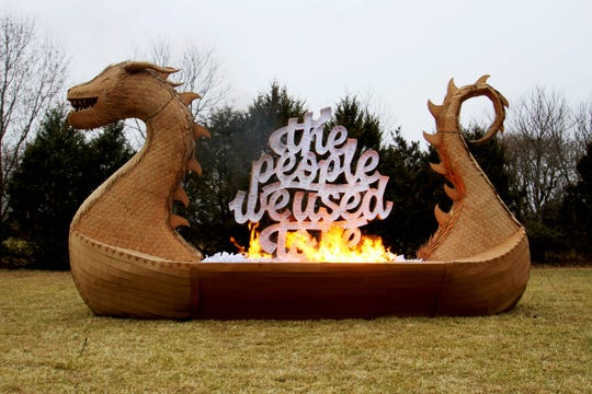 A cardboard Viking ship begins burning in a field Dec. 14, 2019.