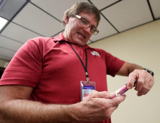 Leon County Schools assistant superintendent Alan Cox reads the label on a bottle used for vaping.