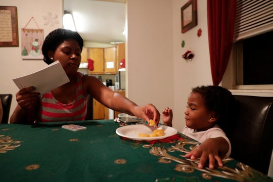 Linda Johnson, a resident, tries to get her daughter J'amoria Johnson, 2, to eat her dinner during bible study at Making Miracles group home Monday, Dec. 9, 2019.