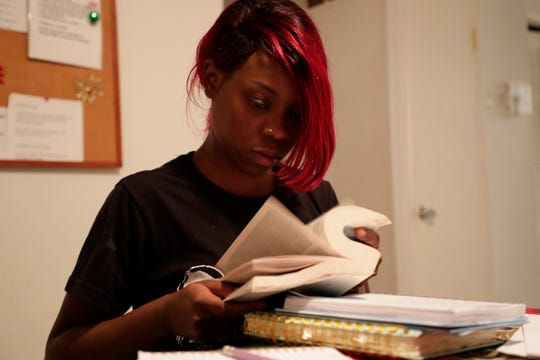 Michelle Bryant, a resident, pages through her bible during bible study at Making Miracles group home Monday, Dec. 9, 2019.