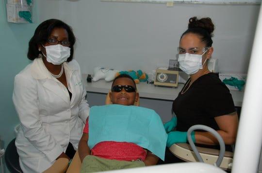 Little Lights Dentistry presiding dentist Dr. Macdalie St-Preux, left, with patient Owen Linares,6, and Janel Torres, expanded functions dental assistant.