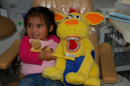 Two-year-old Fergi Lopez Morales shows off her tooth brushing skills on Smiley, the Little Lights Dentistry dog.