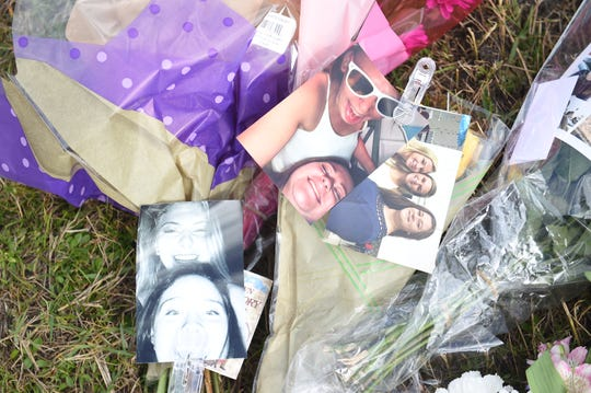 People gather Tuesday, Feb. 7, 2018, at the site of the fatal car crash on Okeechobee Road in western St. Lucie County that killed two teens, Santia Myriah Feketa, 18, of Fort Pierce, and Britney Lee Poindexter, 16, of Port St. Lucie.