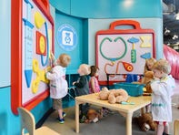 A group of children play together in the Teddy Bear Clinic area of the Children's Museum of the Upstate.