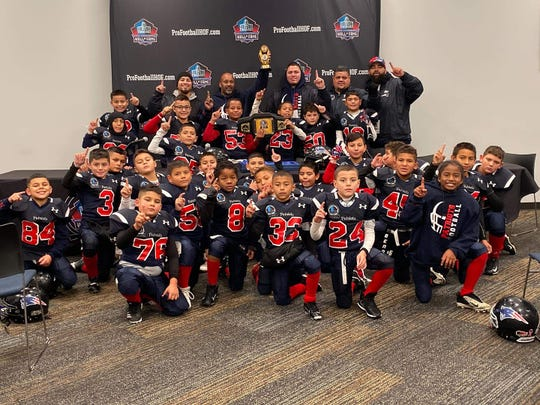 The Tulare Patriots, a junior pee wee youth football team, pose for a photo after winning a national championship on Saturday in Canton, Ohio.