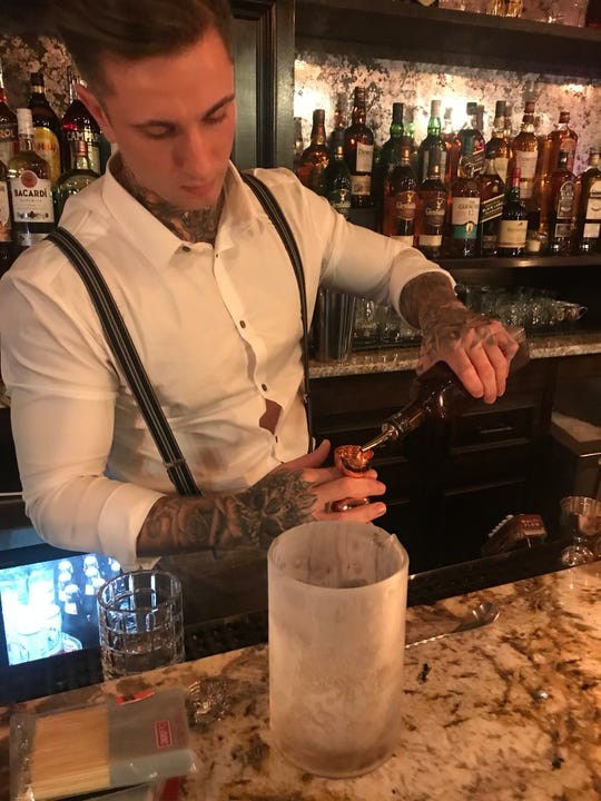 Co-owner Daniel Cahill mixes a drink at The Blind Pig of Westchester in  White Plains.