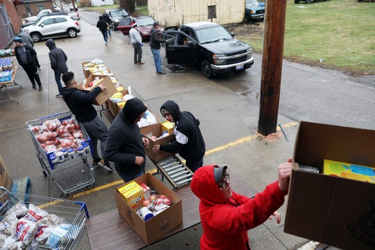 Volunteers from the Maysville High School football program load food boxes during the Salvation Army's distribution day on Tuesday.