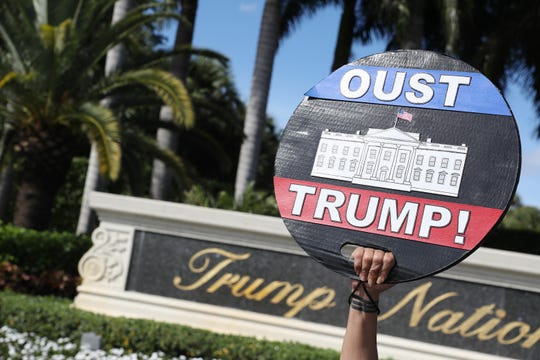 Alessandra Mondolfi holds a sign that reads, 'Oust Trump', as she joins with other protesters outside of the Trump National Doral golf resort urging congress to impeach President Donald Trump on Dec. 17, 2019 in Doral, Florida. The protest is one of many being held across the country calling for President Donald Trump's removal from office on the eve of a House vote that could see the U.S. leader impeached.
