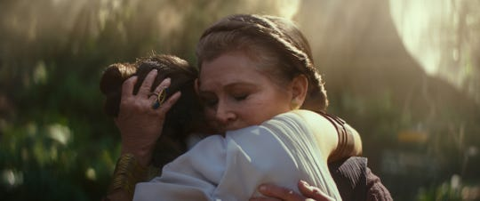 "General Leia Organa (Carrie Fisher) hugs Rey in a moving moment from ""The Rise of Skywalker."" Fisher died in 2016 and is included in the film through unused ""Force Awakens"" footage plus some visual effects wizardry."
