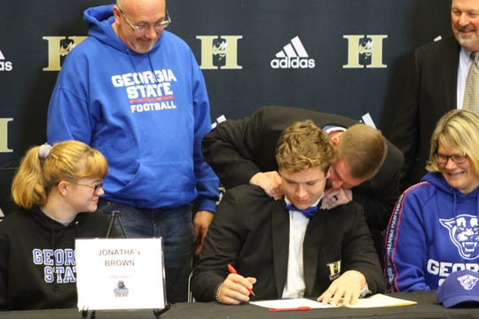 Jonathan Brown gets a hug from coach Jason Tone as he signs with Georgia State on December 18, 2019 at T.L. Hanna High School.