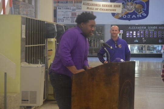 ASH defensive lineman Jacobian Guillory  (left) talks on the podium before signing with LSU Wednesday as Trojans coach Thomas Bachman looks on.