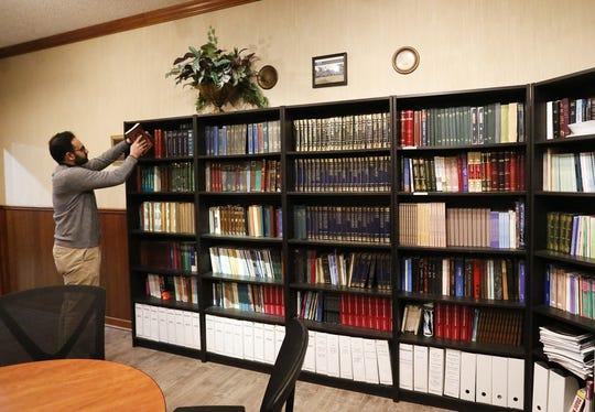 Umair Ahmed, Vice President of the Ahmadiyya Muslim Community's Oshkosh chapter, puts a book away in the library Tuesday at the Masjid Qamar Oshkosh Mosque.
