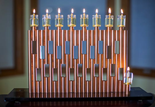 Leib Wolf's menorahs are far from traditional. There is no commandment stating the shape of a menorah. Jewish tradition only states that all of the eight candles must be at the same level.