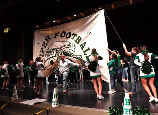 Dennis Montanez leads the Hamlin Pied Pipers football team through a banner during Wednesday's pep rally in the school auditorium. The Pipers are playing in their first state football championship Thursday. Dec. 18 2019