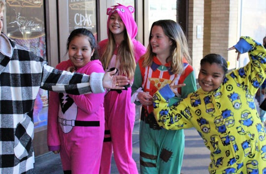 "Four fifth-graders from Abilene ISD's Center for Innovation who attend classes on the McMurry University campus are herded by teacher Marsha Hammack, left, into the Paramount Theatre on Wednesday morning to see ""The Polar Express."" Dressed in their jammies are, from left, Aaliyah Ramirez, Ainsley French, Karma McKelvey and Aaliyah Brown."