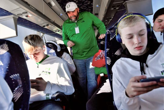Coach Russell Lucas makes his way through the bus taking his Pied Pipers to Arlington on Wednesday for the school's first state championship football game. Lucas has coached in Hamlin for 12 years.