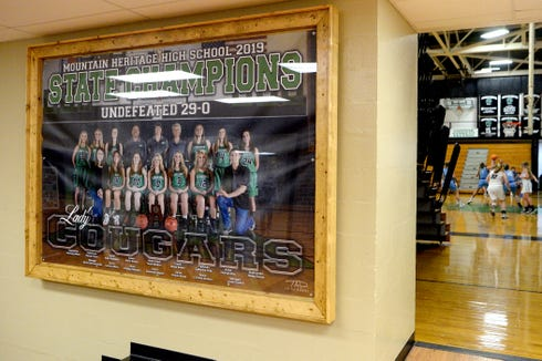 A photo of the 2019 state championship Mountain Heritage girls basketball team hangs outside the gym at Mountain Heritage High School as the team takes on Watauga on Dec. 17, 2019.