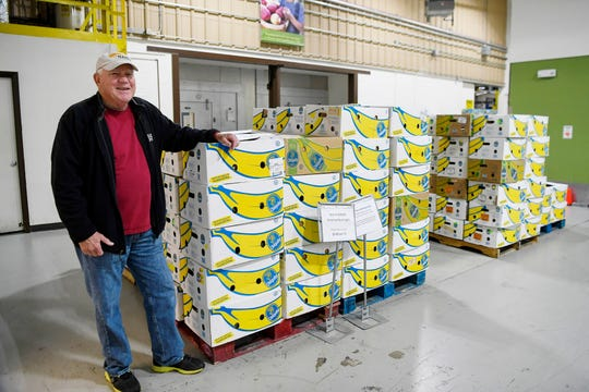 Bill Bass, a volunteer driver with MANNA FoodBank, stands next to boxes of food December 17, 2019.
