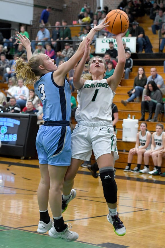 Mountain Heritage's Hannah Tipton goes up for a shot against Watauga's Brelyn Sturgill during their game at Mountain Heritage High School on Dec. 17, 2019.