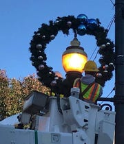A city of Asheville worker hangs a wreath downtown. The city hangs holiday decorations in phases, and they are all up now.