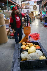 """Merle Cotoio, an employee at Central Kitsap Food Bank, brings in squash and garlic grown by Kitsap Conservation District's GRACE Gardens. The """"Farm to Food Pantry"""" program provides grants to bring fresh produce to the shelves of food banks."""