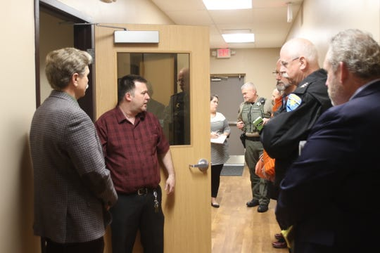 Local leaders listen as Noel Webster (center) leads a tour of the new BAART center in East Bremerton.
