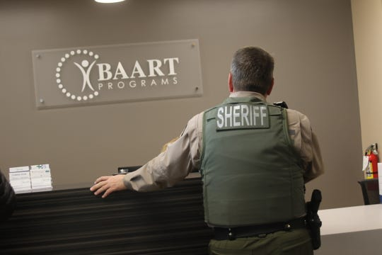 A Kitsap County Sheriff's Office deputy stands at the front desk of the new BAART clinic in East Bremerton.