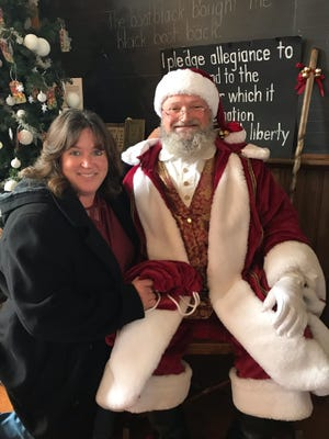 Kriss Kringle, really Chris Whitmore, poses with his wife Melanie during the December 1 Christmas at Harvey One Room School Event.